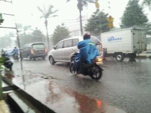 hujan dan pesepeda motor